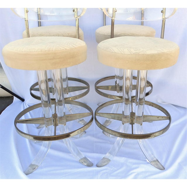 A set of four vintage 1970's acrylic and brass bar stool s by Hill Manufacturing Company. The back upper plate and the...