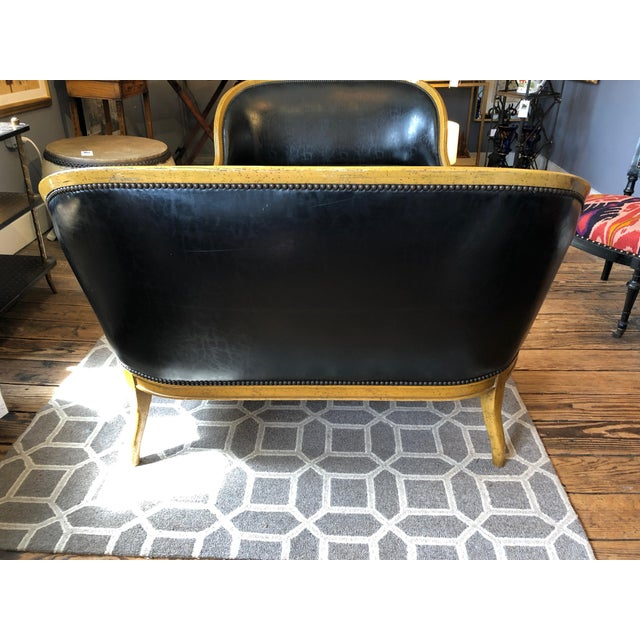 Classic pair of wonderfully shaped loveseats having handsome fruitwood frames and sexy black faux leather upholstery...