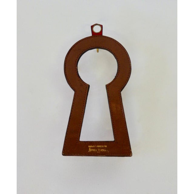 Formed in the shape of a key hole finely stitched red leather hanging key rack . Signed made expressly for Neiman Marcus.