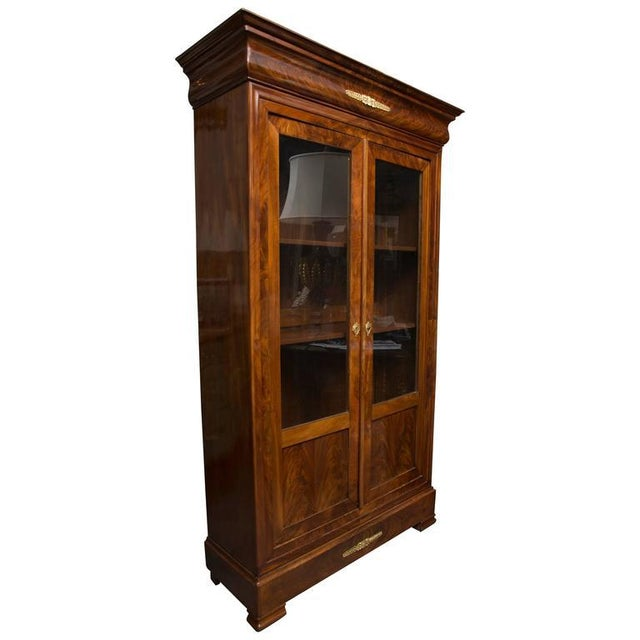 This practical, yet lovely French mahogany bookcase has a prominent shaped cornice above two long glazed doors with wood...
