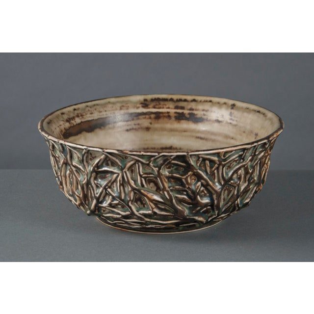 Brown-gray glazed stoneware with blue-gray highlights, depicting branches in relief. Marked on the underside with Royal...