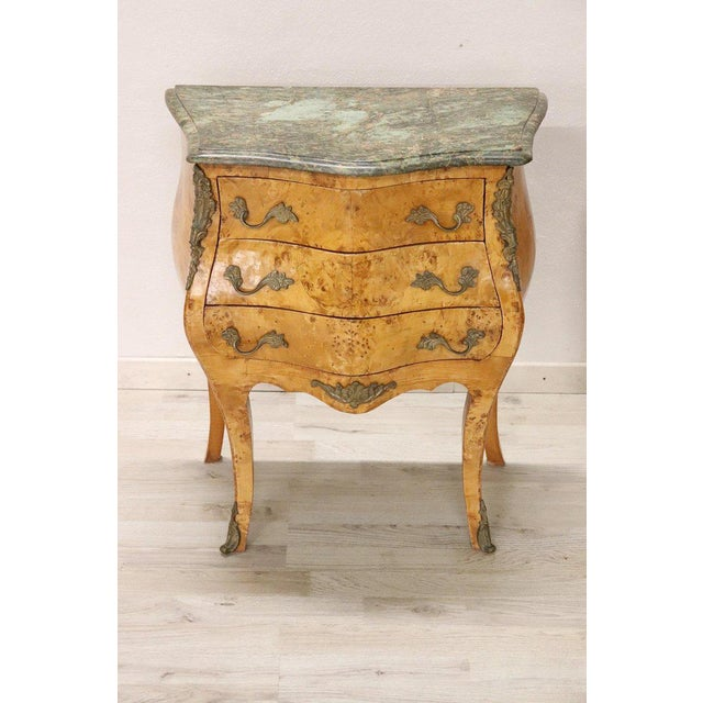 Italian Venetian Louis XV style furniture richly adorned with chiseled bronze. The rare birch wood burl. The top is in...