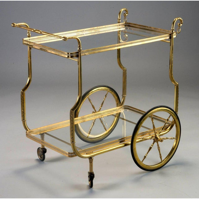 Brass frame trolley has two clear glass shelves with open work brass galleries, circa 1930s. Tray form shelves are not...