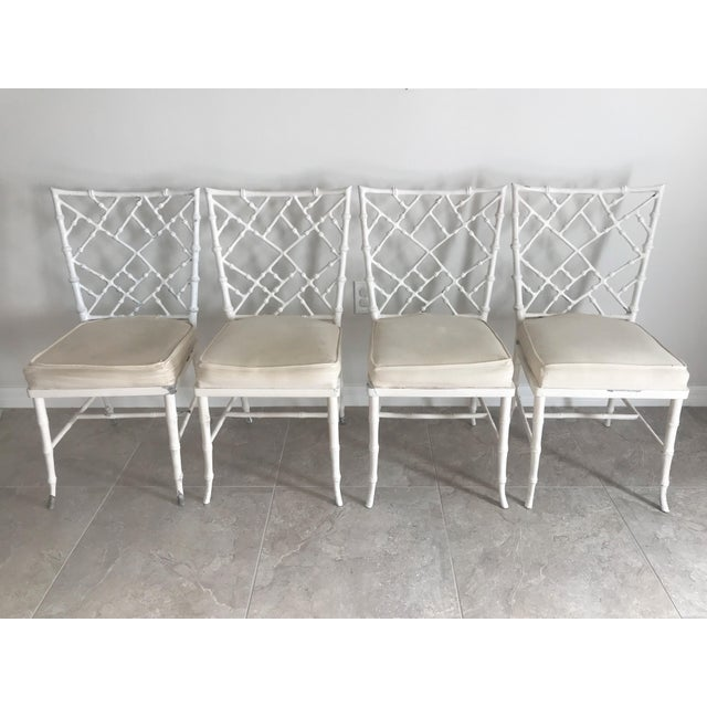 This is a vintage set of four faux bamboo metal chairs in the style of Phyllis Morris. Each has an upholstered seat. They...