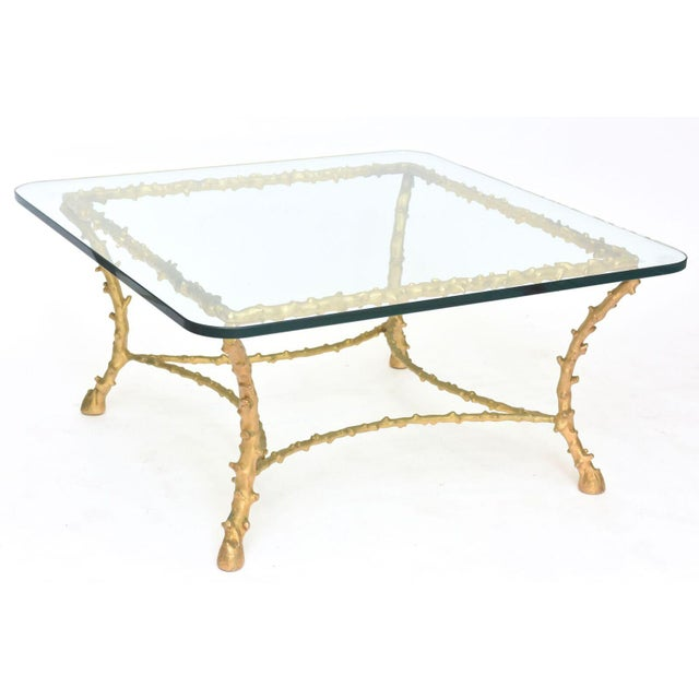 The glass top above a gilt bronze framework with tree branch motif.