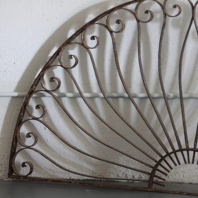Demilune-shaped French iron trellis with curved details. Height: 30.5 in Width: 58 in
