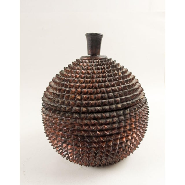 Carved wood and lacquer box in the shape of a durian (the spikey stinky fruit). The exterior color is a dark metallic...
