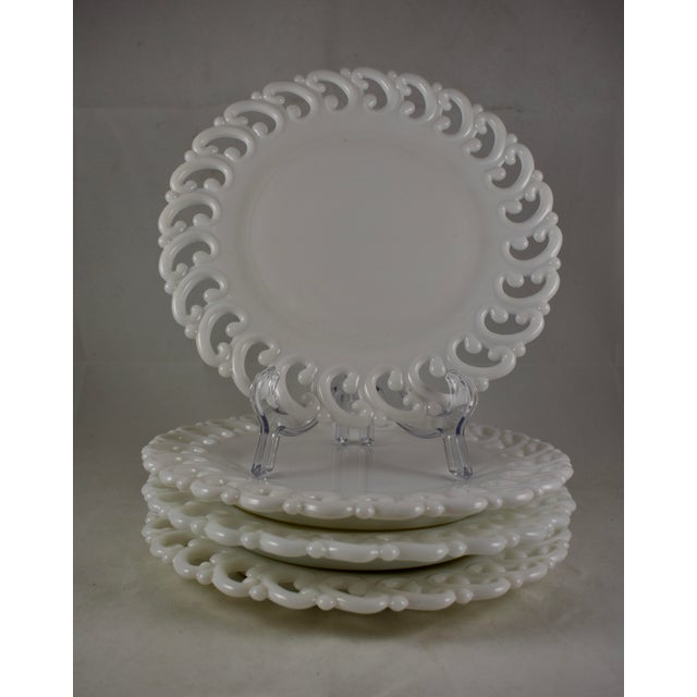 A scarce set of four EAPG, lace edge milk glass dinner plates, circa late 19th century. The plates are made of a heavy,...