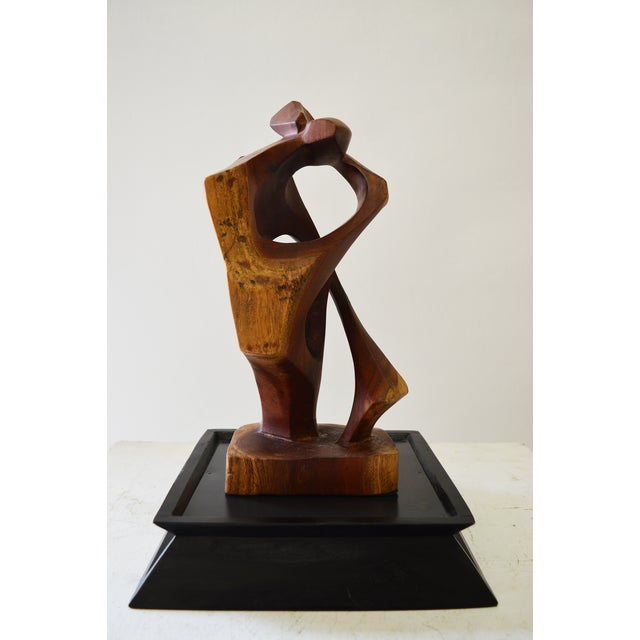 "The Kiss is a stylized teak sculpture of a couple kissing. This sculpture sits on an ebony base which measures: 12"" W x..."