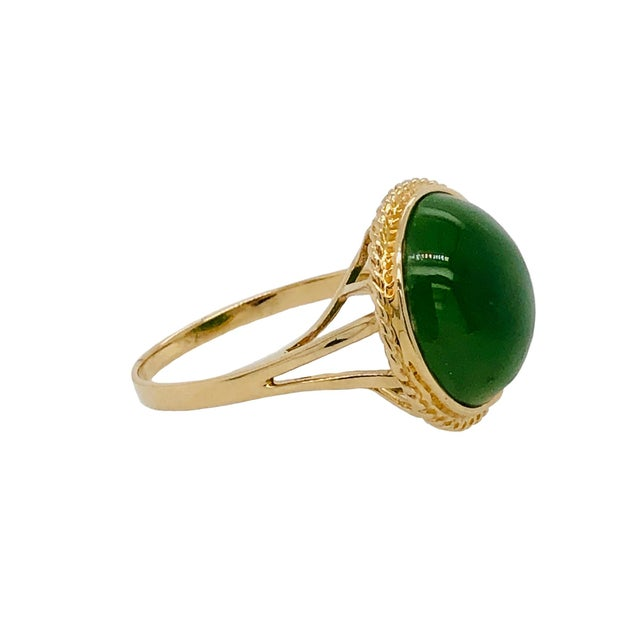 A fine vintage 14K yellow gold ring featuring a cabochon jade with a gold bezel and basket mounting. The ring is marked...