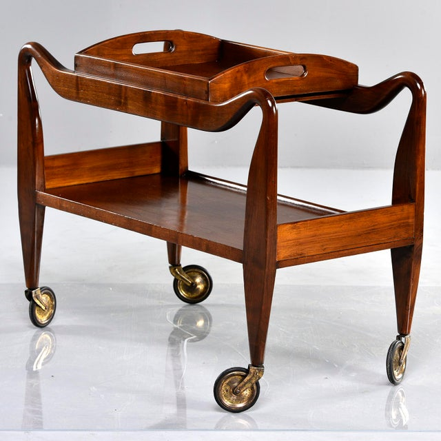 Italian trolley or tray table on casters. Walnut frame has dramatic curves, lower shelf, original casters and removable...