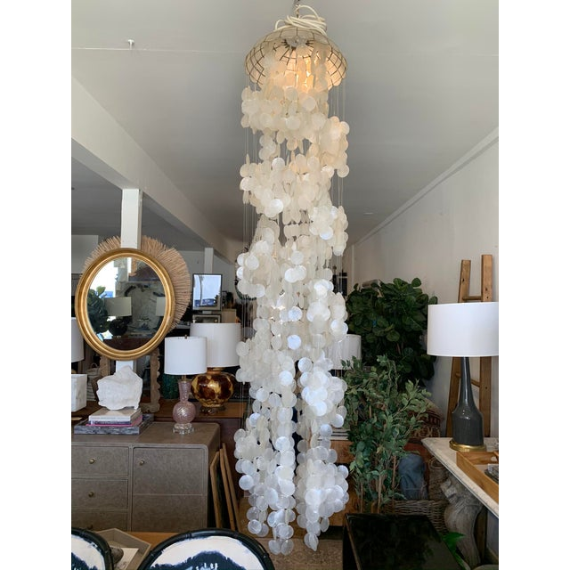 Conjure seaside romance and boho chic with this eye catching capiz shell chandelier. Adorned with strands of dangling...