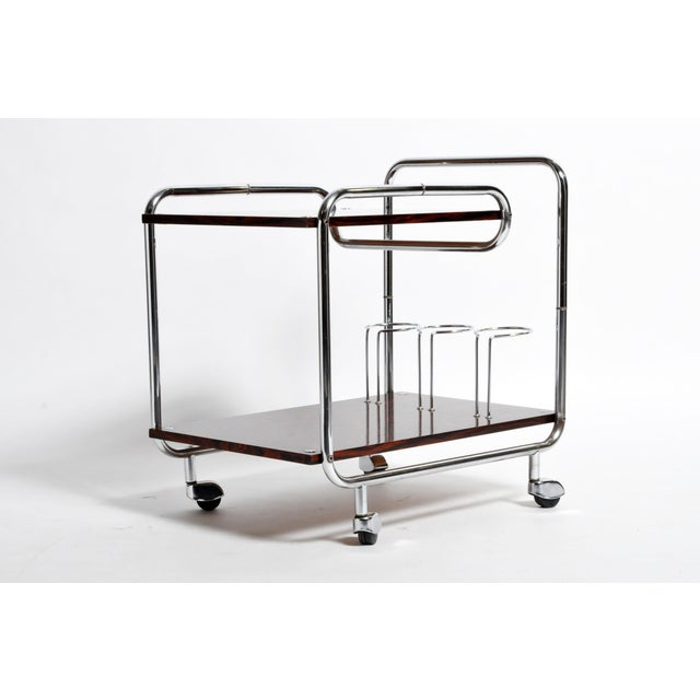 This elegant bar cart is from Hungary and was made from rosewood and chrome, circa 1960. The bar cart features 2 shelves,...