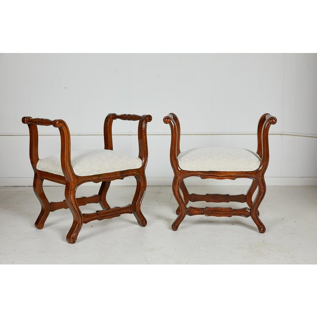 Early 20th Century Italian pair of carved walnut stools in the provencal style with upswept and turned arm rests and an...