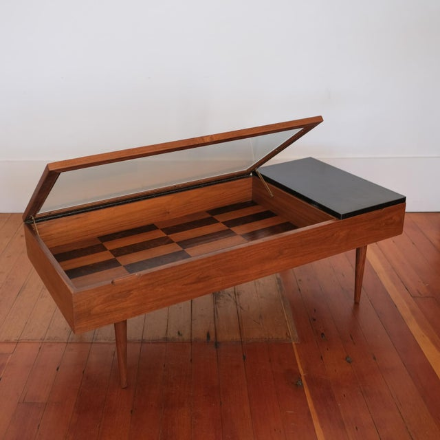 Walnut and rosewood coffee table by Stewart MacDougall for Glenn of California. There is a vitrine side for display and a...