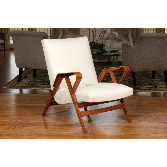 A unusually beautiful pair of vintage lounge chairs, circa 1950s. Handsome maple frame construction with a lovely bent arm...