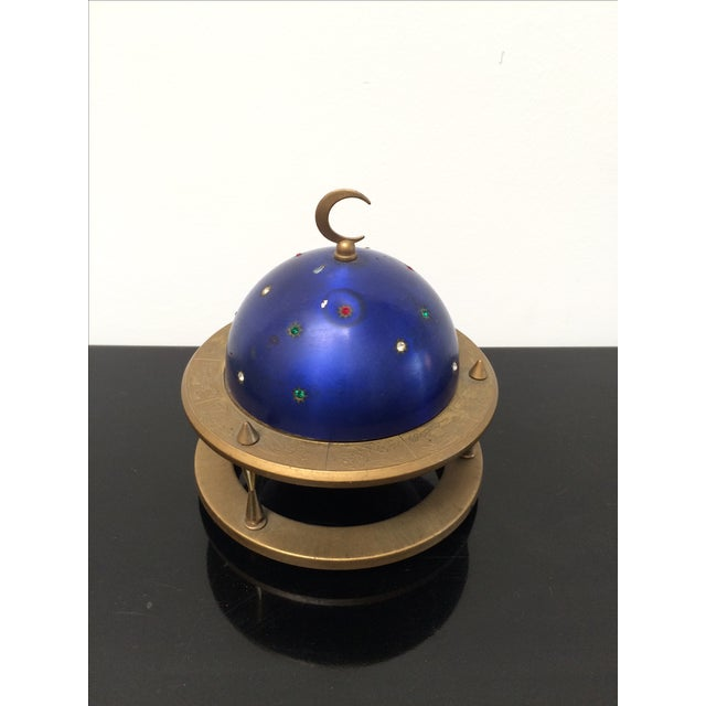 Unusual pop-up cigarette holder in the shape of a globe / planet surrounded by a Saturn like brass ring with incised...