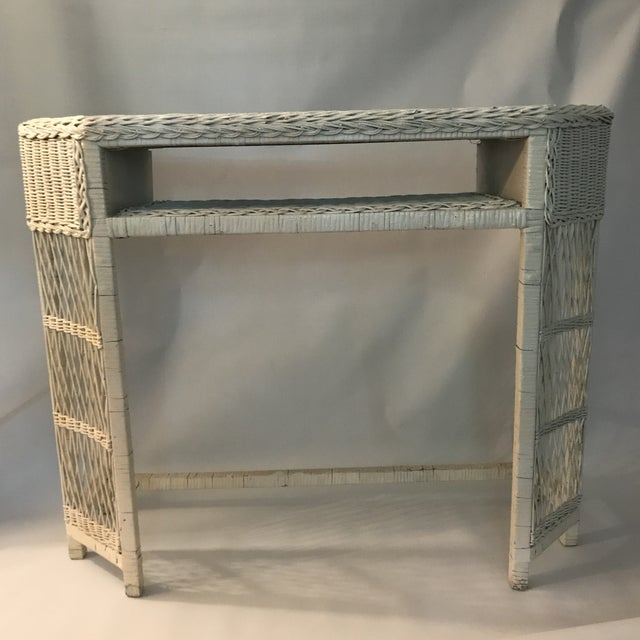 Vintage white painted wicker narrow console or dressing table / vanity. One open shelf above kneehole opening.