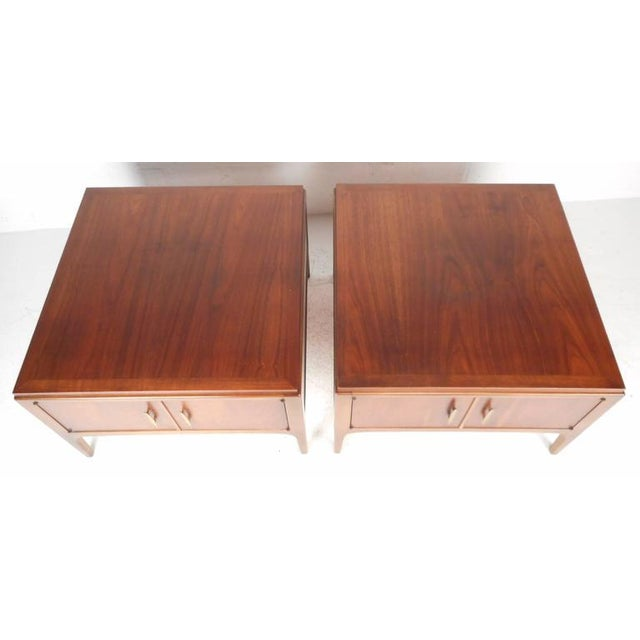 Impressive Mid-Century pair of Lane end tables feature sculpted brass pulls and finished backs. The oversized design...
