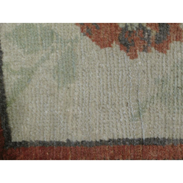 This beautiful vintage Turkish Oushak rug is hand-knotted, 100% wool, made in Turkey, Ushak region. It features a floral...