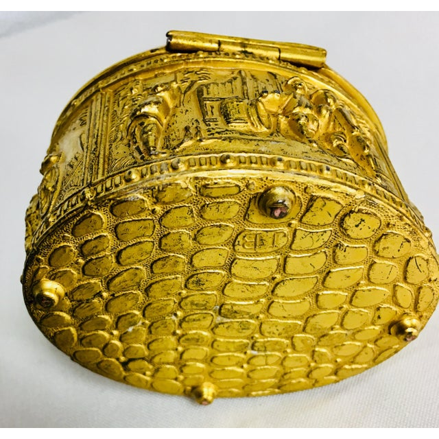 This is a gilded French ring box.The exterior of the box has raised people in the village scenes. The interior of the box...