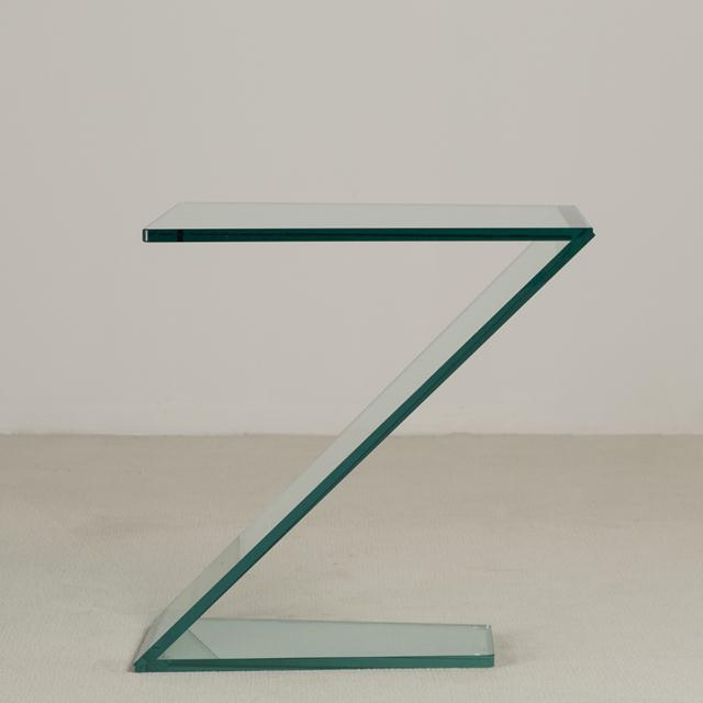 A Cantilevered Sculptural Glass Side Table Dimensions provided is top surface, Footprint is 25cm x 42cm NB: These items...