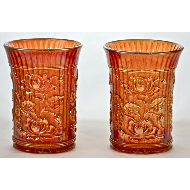 Pair of antique iridescent marigold glass vessels, vases or catchalls with a detailed rose pattern and fluted body which...
