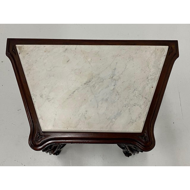 A lovely vintage side or end table with an interesting skewed rectangular shape and ornately carved mahogany base with...