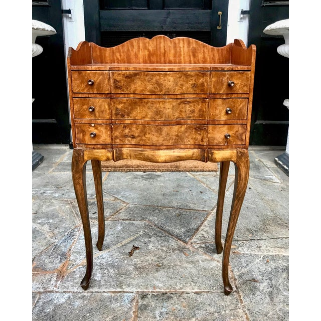 A good looking Louis XV style cabinet having three serpentine shaped thin drawers residing over dramatic and thin cabriole...