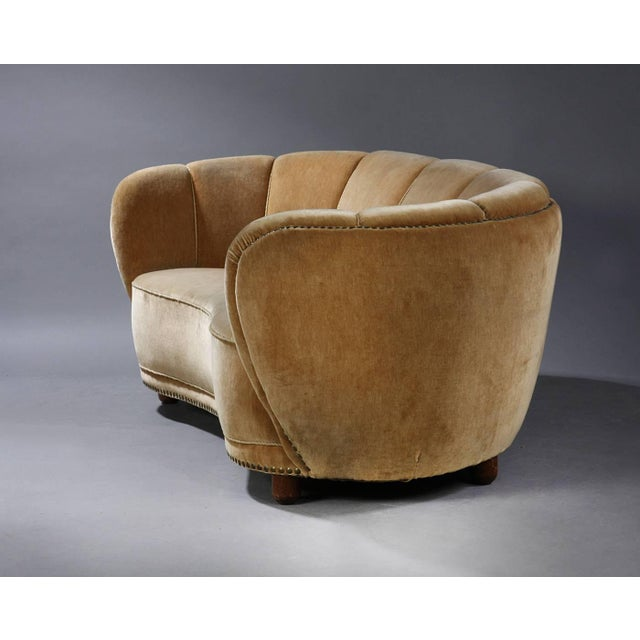 A wonderful banana shaped curved sofa, in the style of Viggo Boesen and Fritz Hansen, made in Denmark, 1940s. The...