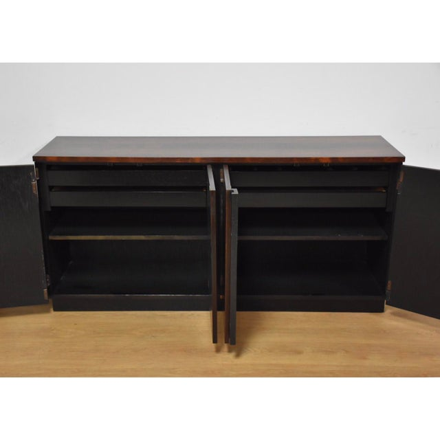 A mid century modern four door rosewood and black lacquered credenza with shelving and drawers. Professionally restored....