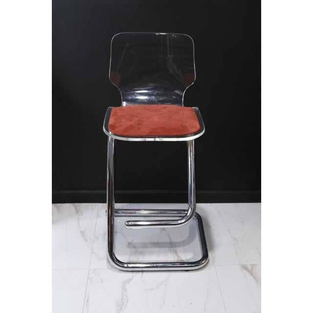 Pair of Lucite bar stools with orange suede seats on chrome frame with floating footrest. Made in the 1970s.