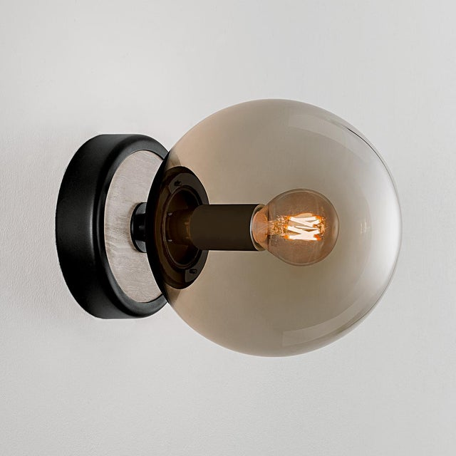 Satin black with smokey glass wall lamp with natural stone and opal glass. The glass globe is secured with a threaded...