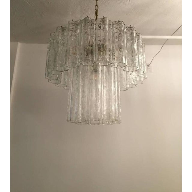 Mid-Century Modern Italian Tronchi chandelier. Each Tronchi is solid glass, measuring 12 inches and 8 inches. They hang...