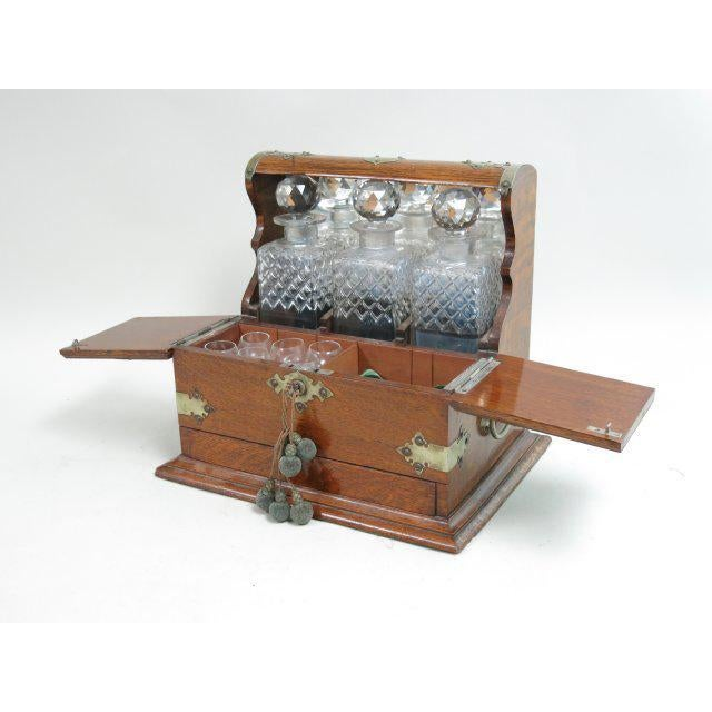 A Victorian tantalus set complete with six shot glasses, three crystal bottles, and a secret compartment with key. This...