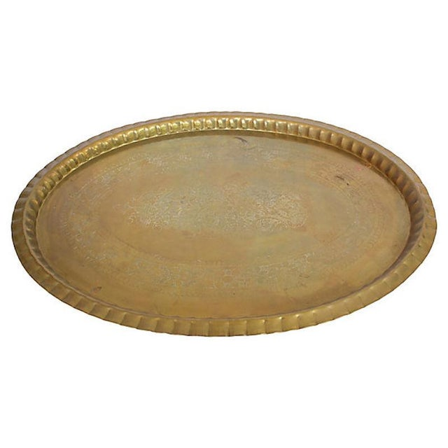 Large Moroccan brass tray with engraved motif and ribbed gallery edge. Hardware on back to allow tray to be displayed on...