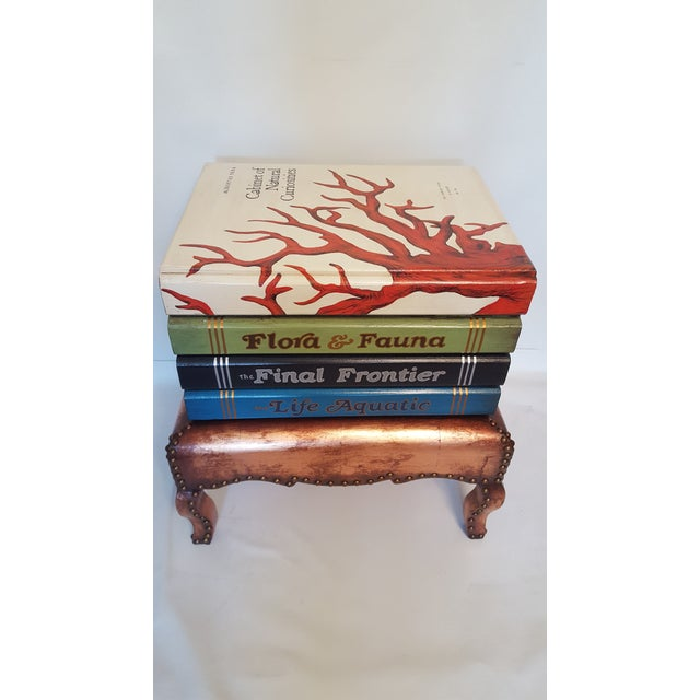 Hand-painted accent table shaped as a stack of large books. On the top is a representation of the coral topped coffee...