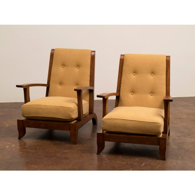 A handsome pair of 1940s French lounge chairs in oak and Belgian linen.