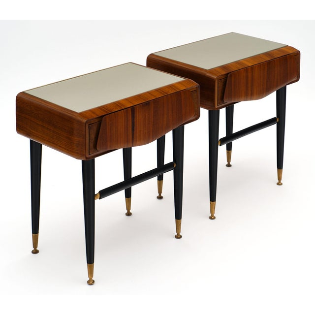 Italian mid-century side tables each featuring a drawer and a gray colored glass top. The base is ebonized with gilt brass...