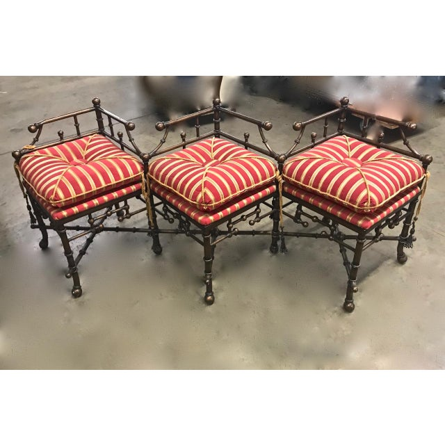 This is a unique 20th century triple seat iron and brass faux bamboo bench that has been beautifully upholstered in a silk...