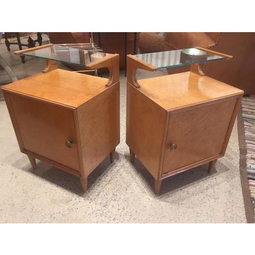 Wonderful pair of vintage French mid-century nightstands. Very stylish mid-century design, each feature a door and glass...