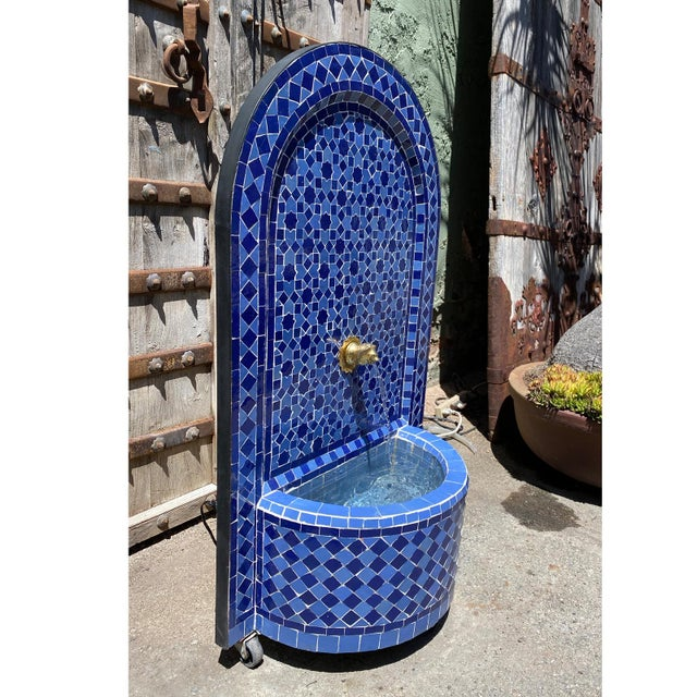 Stunning hand cut and crafted Moroccan arch wall fountain in vibrant blue ceramic tile. Intricate detailed brass faucet....