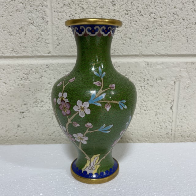 This is a great mostly kelly green vase with a floral design. Typical brass lining and rim. Excellent condition. Sticker...