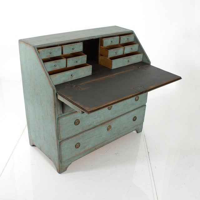 Early 1800s. A small blue-painted bureau with blackened drop-leaf writing tablet and blue-painted interior fittings, lower...