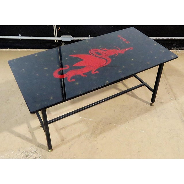 Oriental smoked glass top coffee table with a dragon design on a metal frame with brass feet.