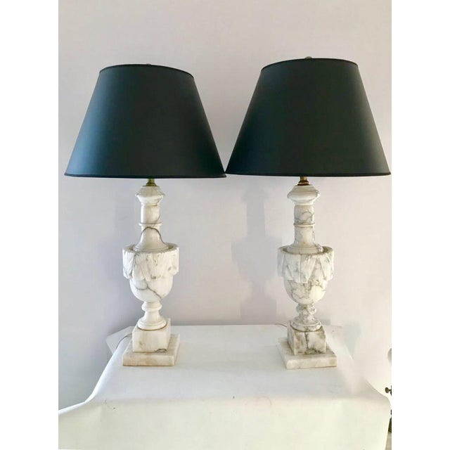 Pair of antique Italian hand carved urn shaped Carrara marble table lamps with white finials, lamps are same style,...