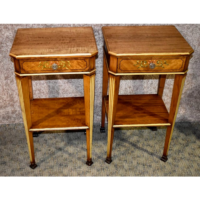 Pair of side tables have a French style. The wood is satinwood. The tables have painted designs on the drawer fronts....