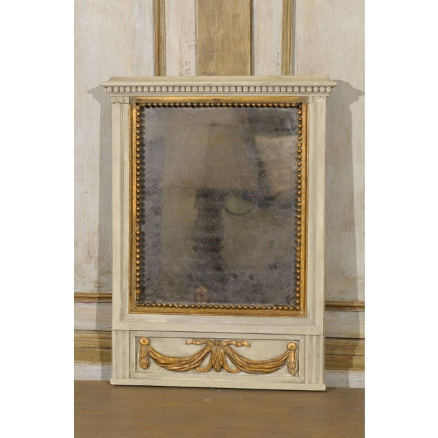 A French mid-19th century small antiqued mirror, circa 1850. This mirror is adorned with a swag motif that runs across the...