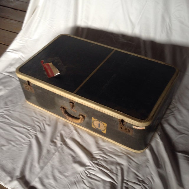 This is an exceptionally large vintage suitcase. It's hard sidded in dark blue with off white trim. It has lots of...