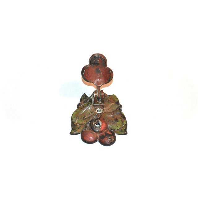A 1920s cast iron door knocker made in the USA by Hubley. It features cherries and leaves, with their original red and...